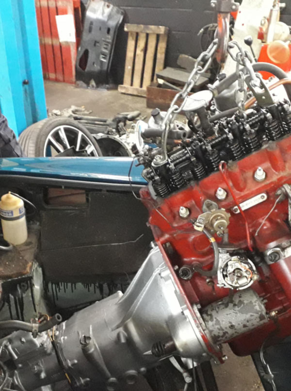 transmission being installed into a classic mg
